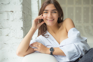 a portrait of a young, pretty sexy, charming girl in a white man's shirt sitting on a white sofa near the window in a bright room with a loose long hair
