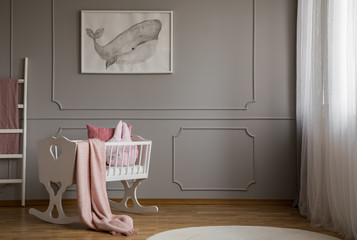 Whale on poster on the empty grey wall of cute baby bedroom interior with white cradle with pillow and paste pink blanket