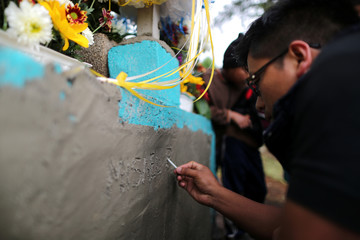 A man inscribes the grave of Misael Paiz at his funeral in Aguacate