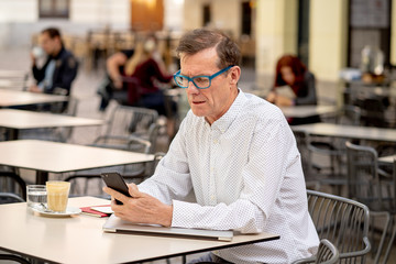 Smiling attractive stylish mature man using smart phone working online sitting outside coffee shop