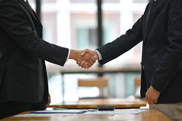 Business people shaking hands while  finishing up a meeting in boardroom