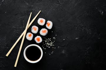 Fototapeta Sushi roll maki with salmon. Japanese cuisine. Top view. On a black stone background. obraz