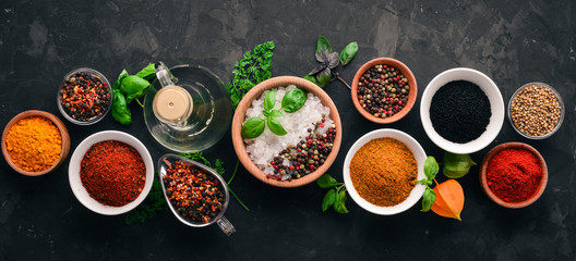 A set of spices and herbs on a stone table. Indian traditional spices. Top view. Free copy space.