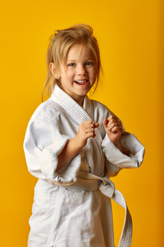 Little serious girl wearing white fighter kimono and standing in pose on yellow background