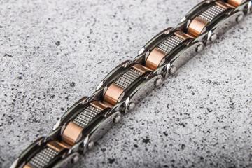 Steel bracelet on concrete background