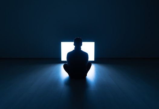 The male sitting in the dark room in front of a television