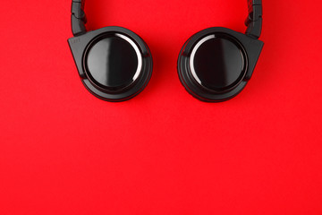 Black headphones on the red background. Music concept.