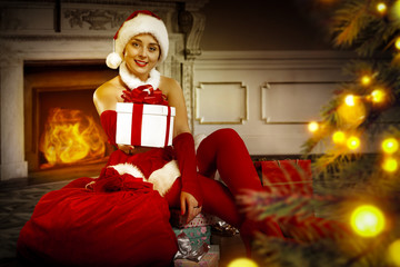 Slim young santa claus woman with christmas tree decoration and background of fireplace