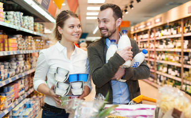 Couple is standing with milk in supermarket