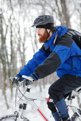 Determined young man with long beard riding a mountain bike through deep powder snow in a forest. Side view. Active sport lifestyle in cold weather.