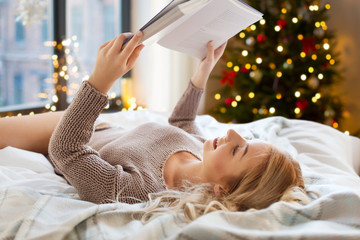 Fototapete - holidays and people concept - happy young woman reading book in bed at home over christmas tree lights on background