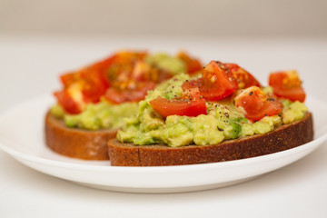 Avocado toast. Healthy toast with avocado mash and cherry tomatoes on a plate.