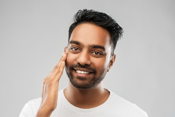 grooming, skin care and people concept - smiling young indian man touching his face over grey background