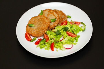 Potato pancakes with fresh mix of salad on a plate close-up.