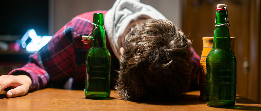 young drunk man with glass and bottle of alcohol lying on the table  f