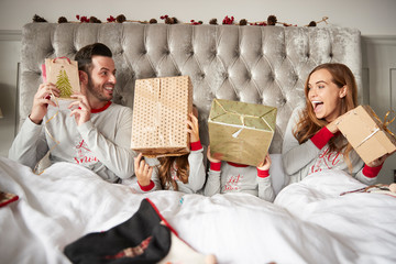Excited Family In Bed At Home Shaking Gift Boxes On Christmas Day