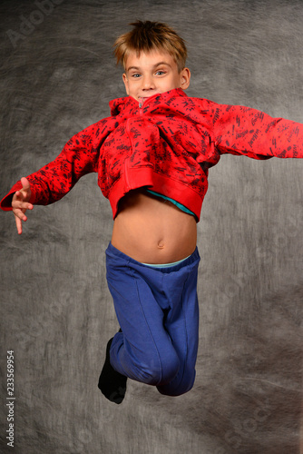 A boy in a red sweater and blue pants jumps and holds his