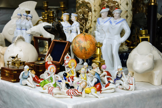 Figurines of ladies in swimsuits, antique globe, figurines of sailors, etc. for sale at flea market in Paris. Flea markets are very popular type of entertainment in France. Vacation concept.