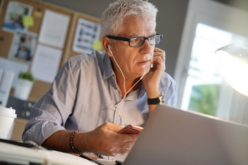 Mature man in office, using smartphone and earphones