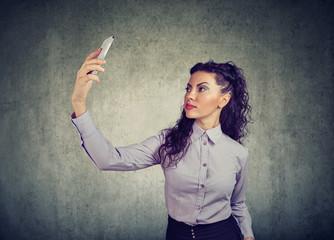 Modern businesswoman taking selfie with phone