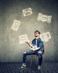 skillful man sitting on chair and juggling with electronic devices icons