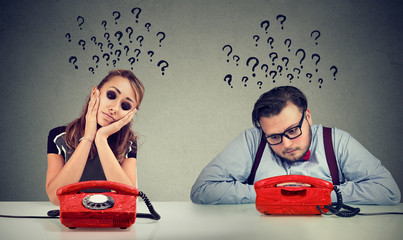 Sad man and woman waiting for a phone call from each other have many questions