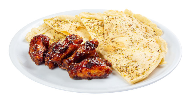 beer snack on the white plate. grilled chicken wings with italian pita bread chips