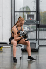 attractive muscular sportswoman training with dumbbell in gym