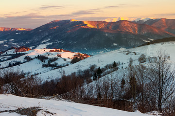winter countryside of Carpathian mountains. beautiful landscape at sunrise. rural fields on a hill covered in snow. snowy peak of distant ridge shine on the sun light. valley in blue shade