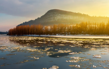 floating of ice on the river tisza in winter. lovely Carpathian landscape with leafless trees on the shore and high hill in the distance