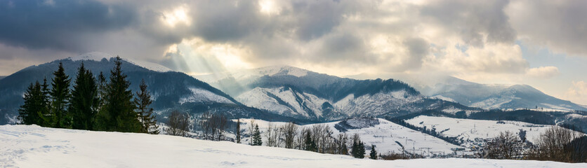 panorama of a mountainous countryside in winter. small forest on the hill and village down in the valley. snowy tops of the ridge beneath the gorgeous cloudy sky