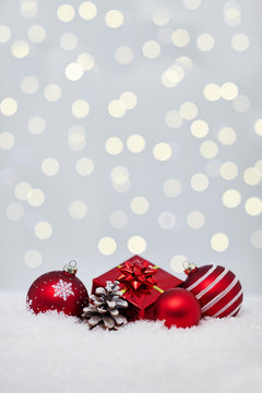 Christmas red balls on snow with bokeh lights