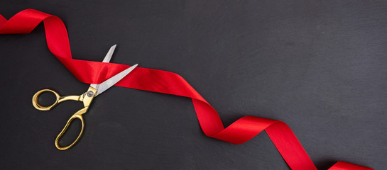 Scissors cutting red silk ribbon against black background, banner.