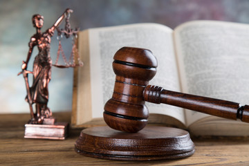 Judge gavel and statuette of justice and book background law