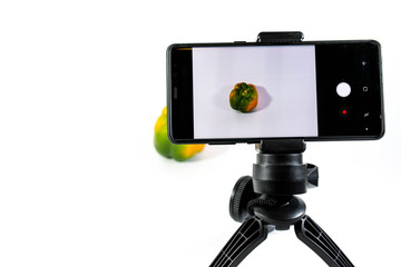 Photographer creating image with a modern mobile phone on small tripod green yellow pepper in focus on white background.