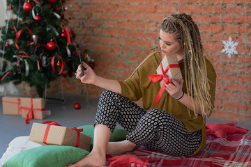 happy young beautiful girl talking on the phone or taking a selfie with her gift. shopping for christmas. uses the smartphone to write a thank you message for the gift.
