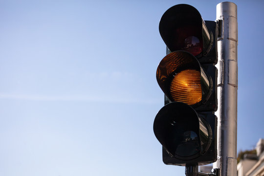 Amber, yellow traffic lights for cars, blue sky background