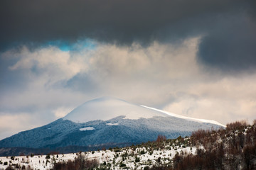 dramatic sky above the distant snowy peak. beautiful winter scenery