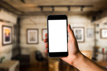 Mockup image of hand holding white mobile phone with blank white screen in cafe.