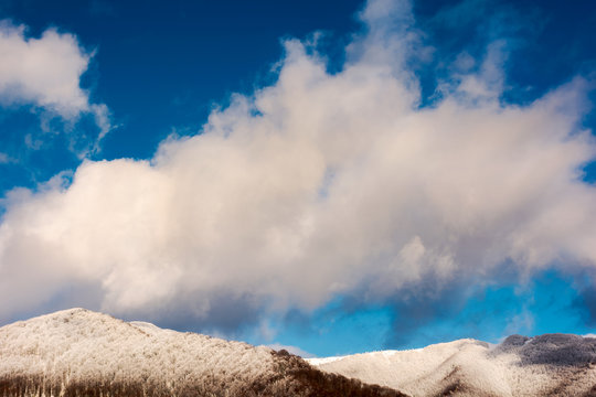huge fluffy cloud abow the forested hill in snow. wonderful winter nature background