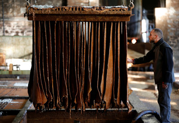 An employee checks pieces of leather to make shoes and boots at the Tannery Bastin of shoemaker J.M. Weston in Saint-Leonard-de-Noblat