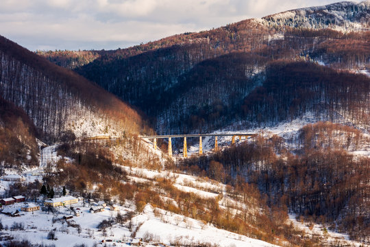 winter rail road transportation in mountains. station and village on hill and viaduct in the distance. beautiful scenery in dappled light