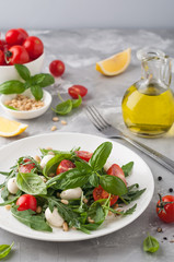 Healthy salad with cherry tomatoes, arugula and mozzarella. Home made food. Concept for a tasty and healthy appetizer. Selective focus.
