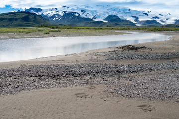 Katmai National Park with river, beach, sand and mountains with glaciers. Sunny summer day in Alaska. Bear footprints in the sand