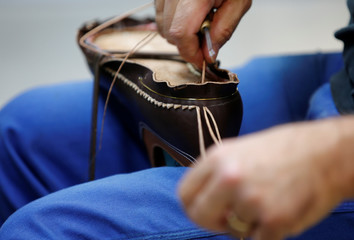 An employee stitches a leather shoe at the shoemaker J.M. Weston factory in Limoges