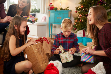 Excited Family In Lounge At Home Opening Gifts On Christmas Day