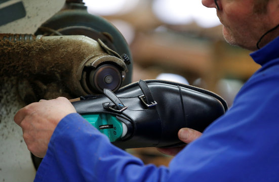 An employee works on the leather sole of a shoe at the shoemaker J.M. Weston factory in Limoges
