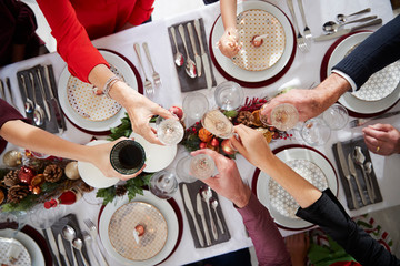 Overhead Close Up View Of People Making Toast Over Table Setting For Christmas Meal At Home