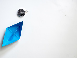 Blue paper boat with compass