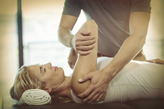 Woman receiving shoulder therapy from physiotherapist